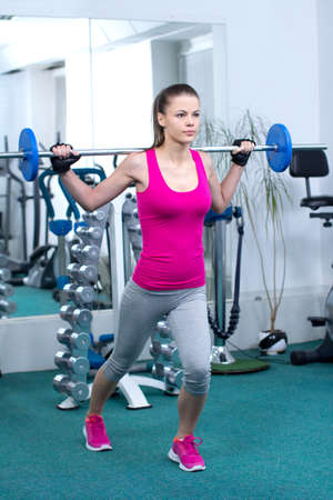 Fitness Woman. Attractive young woman is engaged in fitness sport club photo