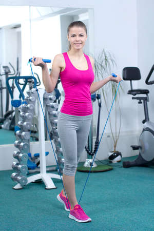 Fitness Woman. Pretty sporty girl with skipping rope in gym photo