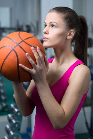 Bascketball Woman. Young beautiful girl holding a ball for basketball in the gym photo