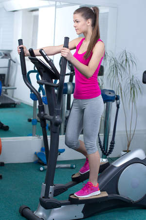 Fitness Woman. Happy woman training at the gym on cross trainer Stock Photo - 23166636