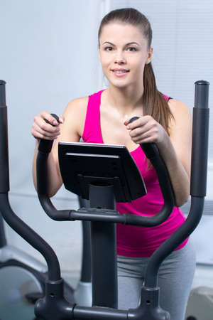 Fitness Woman. Happy woman training at the gym on cross trainer photo