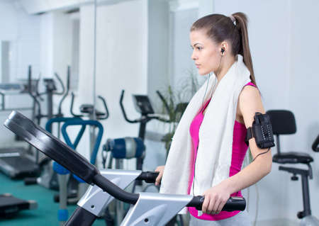 Fitness Woman. Woman runs on a treadmill, exercise in the sport club photo