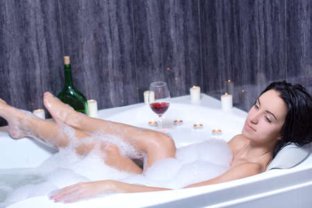A beautiful woman in a bath with foam drinking wine photo
