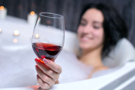 seductress: A beautiful woman in a bath with foam drinking wine Stock Photo