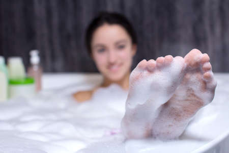 Beautiful smile woman washing leg with pink sponge in bath with foam, young girl bathing in bathtub, relaxing in bath jacuzzi