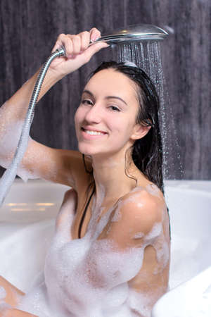 Young beautiful woman taking a bath with foam and washing hair with shampoo photo