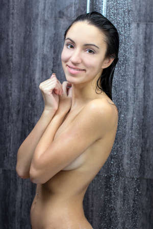 sexy and happy young beautiful woman taking a shower photo