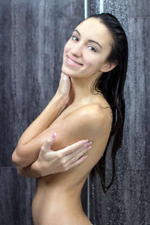 douche: sexy and happy young beautiful woman taking a shower Stock Photo
