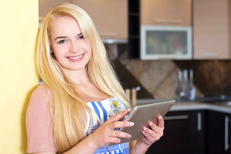 Portrait of a woman using a tablet computer to cook in her kitchen Stock Photo - 23512242
