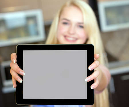 Portrait of a woman using a tablet computer to cook in her kitchen Stock Photo - 23512241