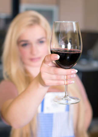 Kitchen Woman. Pretty woman drinking some wine at home photo