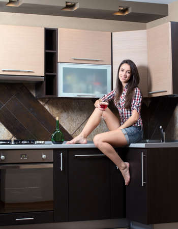 Kitchen Woman. Portrait of cheerful young beautiful woman drinking wine in the kitchen photo