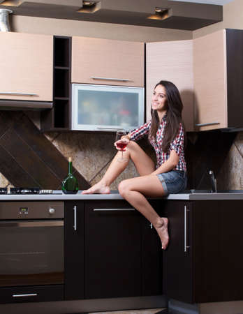 Kitchen Woman. Portrait of cheerful young beautiful woman drinking wine in the kitchen