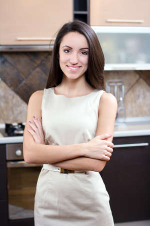 Kitchen Woman. Portrait of young elegant woman drinking wine in the kitchen photo