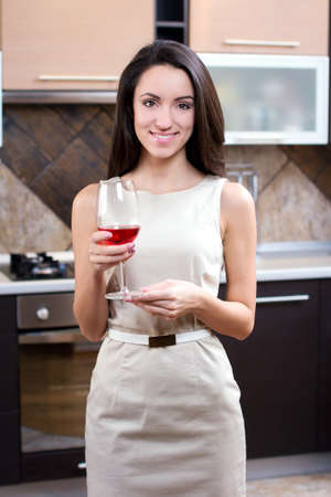 Kitchen Woman. Portrait of young elegant woman drinking wine in the kitchen