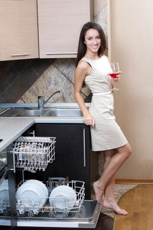 Kitchen Woman. Girl in the kitchen using dishwasher. view of young woman in kitchen doing housework.  drinking wine