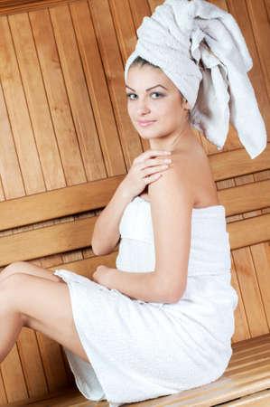 sauna nackt: Spa & Wellness. Frau sitzt auf Holzbank, Entspannung in der Sauna auf Wellness-Center.