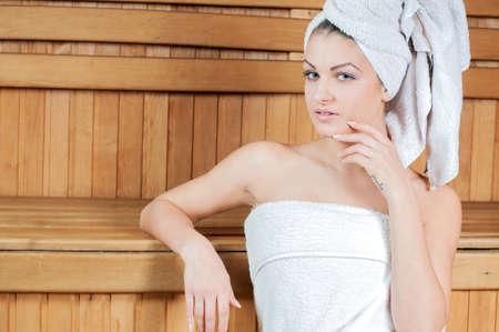 sauna nackt: Spa & Wellness. Frau sitzt auf Holzbank, Entspannung in der Sauna im Wellnesscenter. Lizenzfreie Bilder
