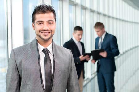 hombre arabe: Retrato de un feliz hombre de negocios asiático en una moderna oficina en un fondo de colegas