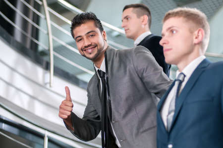 Group of young cheerful business people in business building photo