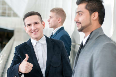 collaborators: Group of young cheerful business people in business building