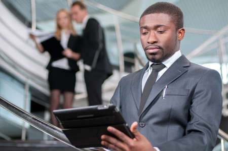 Businessman Using Digital Tablet In Office on the background\ of colleagues