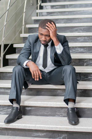A businessman sits on the stairs with his head in hands. photo