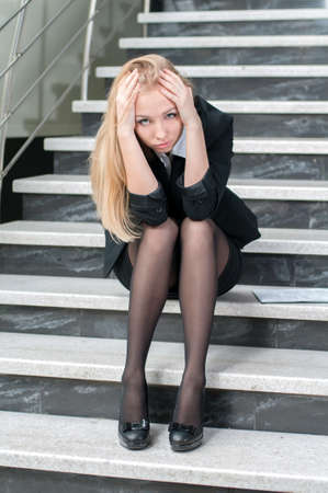 Business woman bored while sitting on the steps of the office. Problems in Business photo