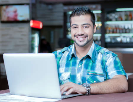 A young Indian guy in a cafe working on laptop photo