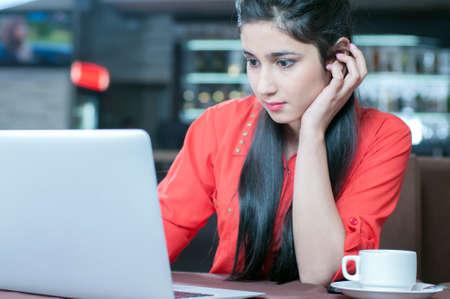 mujer tomando cafe: Joven mujer de negocios indio en una pausa para el caf�. El uso de tablet PC.