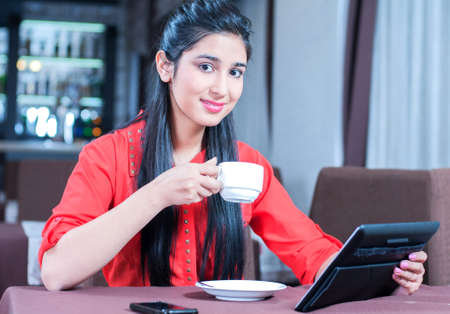 woman in suit: Young indian businesswoman on a coffee break. Using tablet computer. Stock Photo
