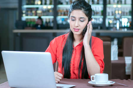 Young indian businesswoman on a coffee break. Using tablet computer. photo