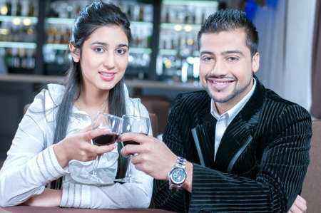 beautiful indian couple with wine glass. Having romantic talk photo