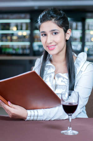 Woman with a Menu. Beautiful Indian descent women holding a Menu while sitting at the restaurant photo