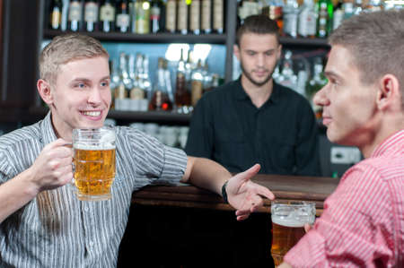 Talking at bar. Two cheerful male friends talking at bar and drinking beer while bartender serving beer at the background photo