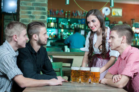 Beer for gentlemen. Beautiful young waitress serving beer while three men sitting at the table in beer pub photo