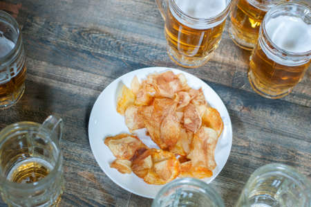Beer mug and potato chips on a wooden table photo