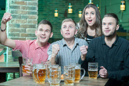 sports bar: Three men and one girl with beer rejoice the victory of their favorite team in the pub Stock Photo