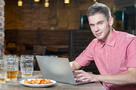 Businessman having a drink while working on his laptop in a beer bar photo