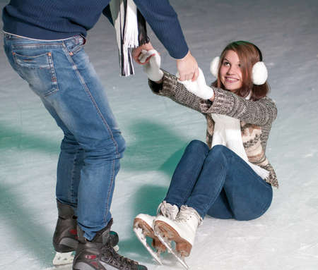 Young beautiful couple smiling on the ice skating indoors ice rink photo