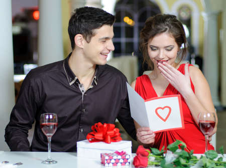 ladies day: Young couple in love make a present to each other on Valentines Day. Stock Photo