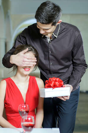 A young man makes a gift to his girlfriend shutting her eyes. Valentines Day photo