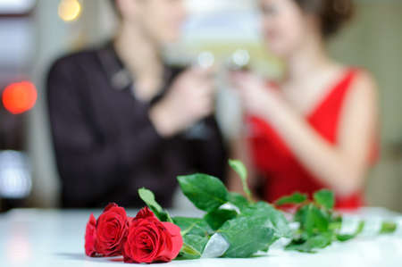 Young happy couple romantic date drink glass of red wine at restaurant, celebrating valentine day Stock Photo