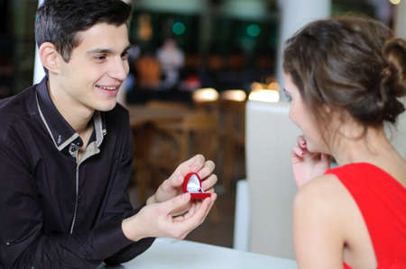 marriage proposal, man give ring to his girl, young happy couple romantic date at restaurant, celebrating valentine day photo