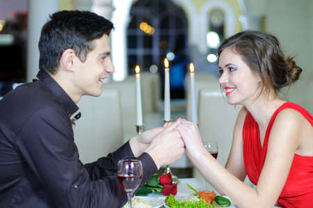 Young happy couple romantic date drink glass of red wine at restaurant, celebrating valentine day photo