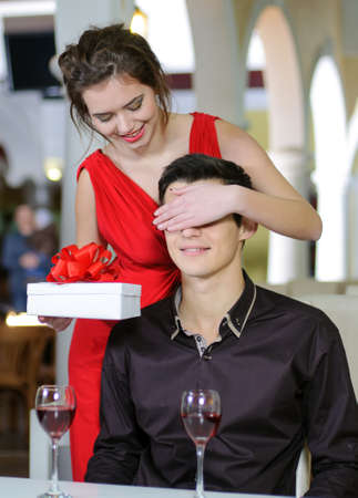 Young couple in love make a present to each other on Valentines Day. photo