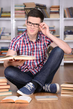 Portrait of a beautiful young student boy reading book in library photo