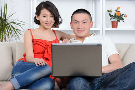 Portrait of young Asian couple sitting on sofa at home, using laptop computer, smiling. photo