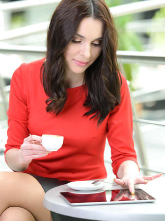 Businesswoman drinking coffee, tea in a coffee shop photo