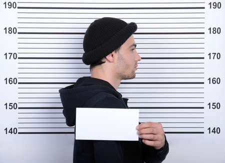 busted: Busted burglar. Angry burglar holding a white poster while standing against police line-up Stock Photo